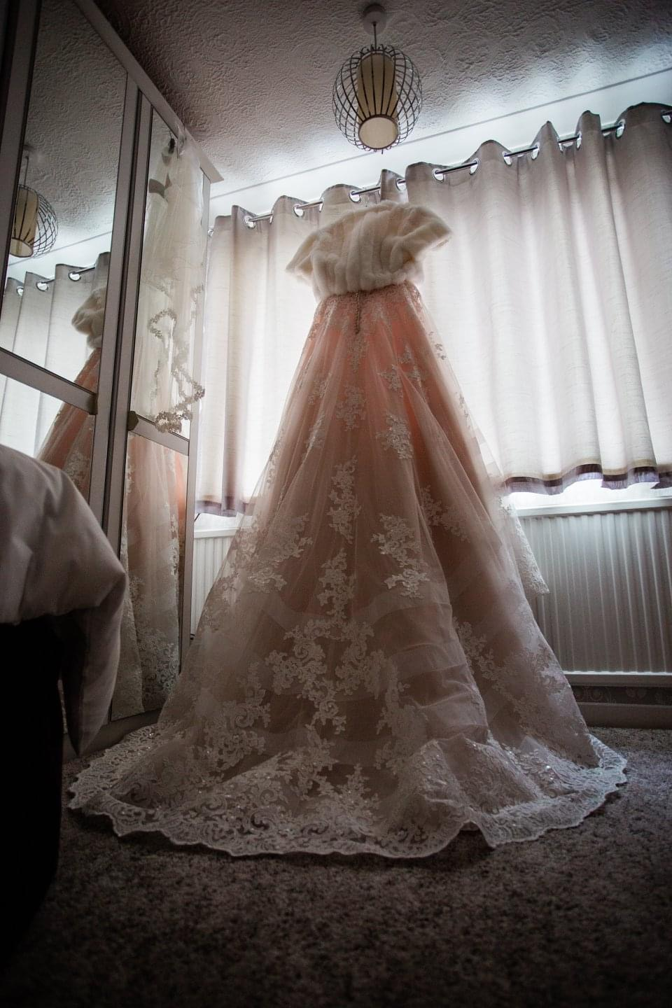 Lizzie Tomkinson's pink lace wedding dress hanging up